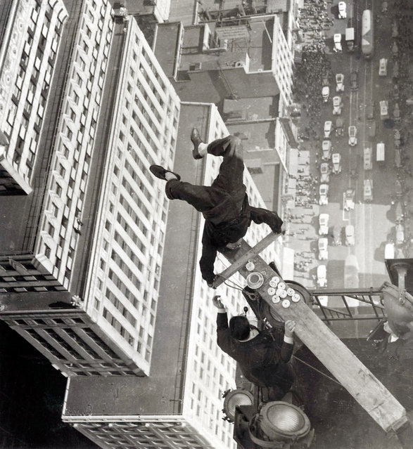 A man balancing on a piece of wood on the roof of a skyscraper. New York, USA, 1939. (Photo by Hulton Archive)