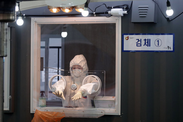 A medical worker wearing protective gear prepares to take a sample at coronavirus testing site in Seoul, South Korea, Monday, January 11, 2021. South Korea's new coronavirus cases dropped to the lowest level in a month on Saturday, but authorities are vigilant over chains of cluster infections coupled with looming concerns over a COVID-19 variant. The country added 641 more COVID-19 cases, including 596 local infections, raising the total caseload to 67,999, according to the Korea Disease Control and Prevention Agency (KDCA). (Photo by Lee Jin-man/AP Photo)