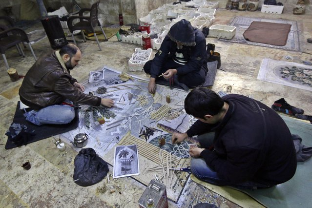 Men work on a mosaic artwork, copied from an original painting, in a workshop in Kafranbel town in the Idlib governorate January 17, 2015. (Photo by Khalil Ashawi/Reuters)