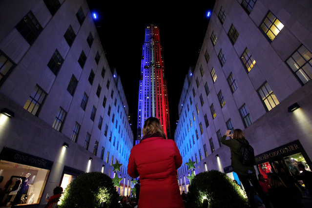 People take pictures of 30 Rockefeller Plaza as it is lit in the colors of the Democratic and Republican parties ahead of the U.S presidential election in Manhattan, New York, U.S., November 7, 2016. (Photo by Andrew Kelly/Reuters)