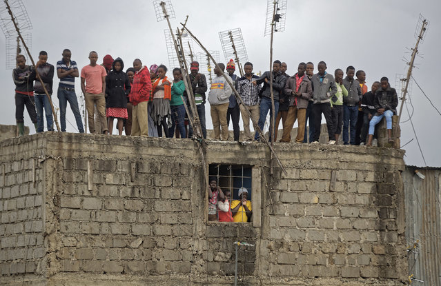 Residents of a nearby building stand on the roof to get a view of the scene of a five-storey collapsed building in the Huruma neighborhood of Nairobi, Kenya Sunday, June 3, 2018. An official from Kenya's Disaster Management Unit at the scene said that two had died, a number were injured, some were still missing, but that many residents of the building had managed to escape before the building fully collapsed. (Photo by Ben Curtis/AP Photo)