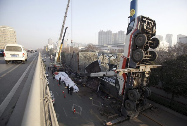 A crane is seen after it overturned in an accident while being used to change an advertisement board in Xi'an, Shaanxi province, January 19, 2015. The driver was injured and sent to hospital after a two-hour rescue, according to local media. (Photo by Reuters/Stringer)