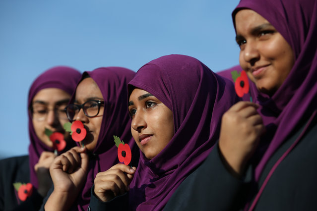 Pupils from Eden Girls' School hold poppies  as they wait to observe a two minute silence in honour of Armistice Day in central London on November 11, 2016. In the run-up to Armistice Day, many Britons wear a paper red poppy – symbolising the poppies which grew on French and Belgian battlefields during World War I – in their lapels. (Photo by Daniel Leal-Olivas/AFP Photo)