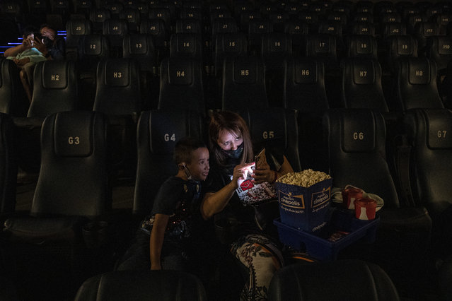 Vivenka Ivanovich and her 6-year-old son Mateo Blanco, wait for the start of a movie at the Cinepolis cinema on the first day after the COVID-19 lockdown in Santiago, Chile, February 18, 2021. The cinemas authorized to open are those located in the communes that are in the intermediate phases of sanitary restrictions. (Photo by Esteban Felix/AP Photo)