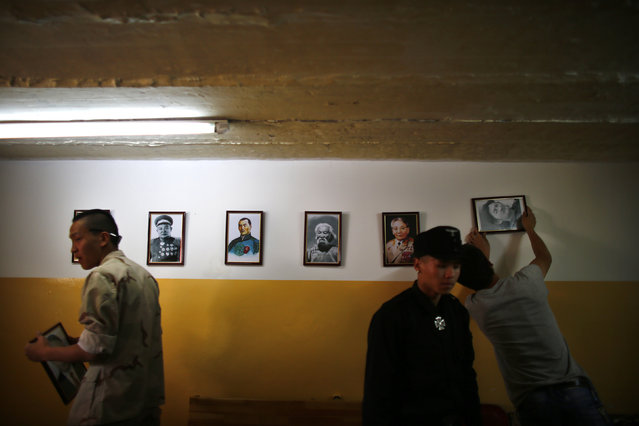 Members of the Mongolian neo-Nazi group Tsagaan Khass hang up portraits of Mongolian heroes at the group's headquarters in Ulan Bator June 24, 2013. (Photo by Carlos Barria/Reuters)