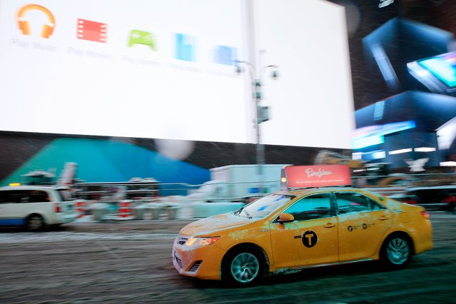A cab drives through Times Square ahead of mandatory street closures on January 26, 2015 in New York City. (Photo by Alex Trautwig/AFP Photo)