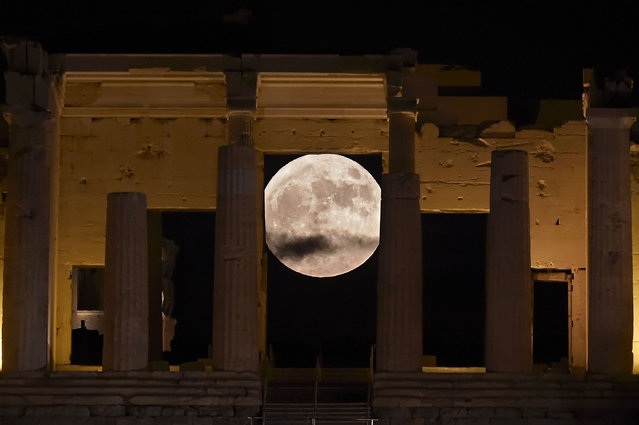 """The """"Supermoon"""" rises behind the Propylaea above the Ancient Acropolis hill in Athens on November 14, 2016. The moon will be the closest to Earth since 1948 at a distance of 356,509 kilometres (221,524 miles), creating what NASA described as """"an extra-supermoon"""". (Photo by Aris Messinis/AFP Photo)"""