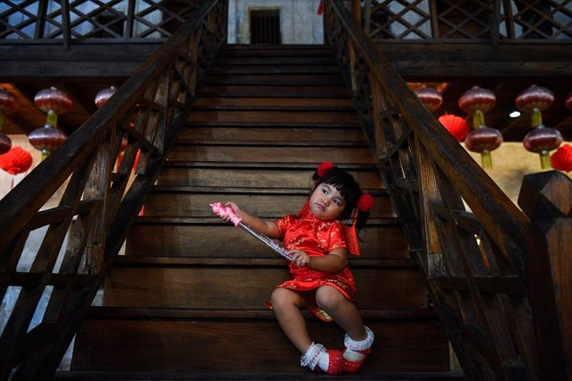 A girl sits on a staircase during Lunar New Year celebrations in Bangkok, Thailand, February 12, 2021. (Photo by Chalinee Thirasupa/Reuters)