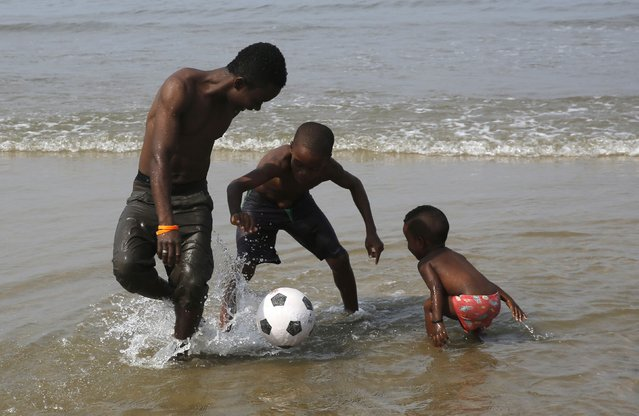 A family plays with a soccer ball on the beach on the Atlantic Ocean coast in Bata, in the Rio Muni region January 23, 2015. The African Nations Cup is being hosted by Equatorial Guinea from January 17 to February 8. (Photo by Amr Abdallah Dalsh/Reuters)