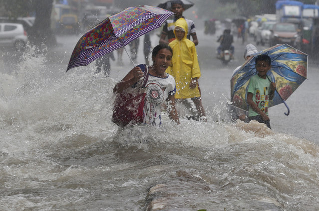 In this Sunday, July 8, 2018, file photo, a woman walking through a water logged street, reacts as a truck driving past creates a wave of ripples prior to drenching her during monsoon rains in Mumbai, India. India's monsoon season runs from June to September. (Photo by Rafiq Maqbool/AP Photo)