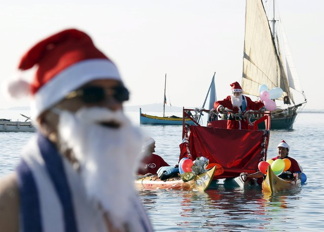 A man dressed as a Santa Claus takes part in the traditional Christmas bath during an unusually warm winter day in Nice, southeastern France, December 20, 2015. (Photo by Eric Gaillard/Reuters)