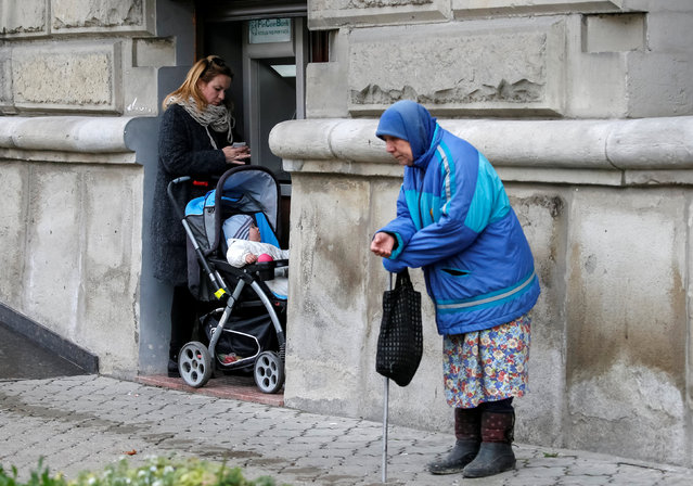 A woman uses an ATM as an elderly woman begs for money in central Chisinau, Moldova, November 12, 2016. (Photo by Gleb Garanich/Reuters)