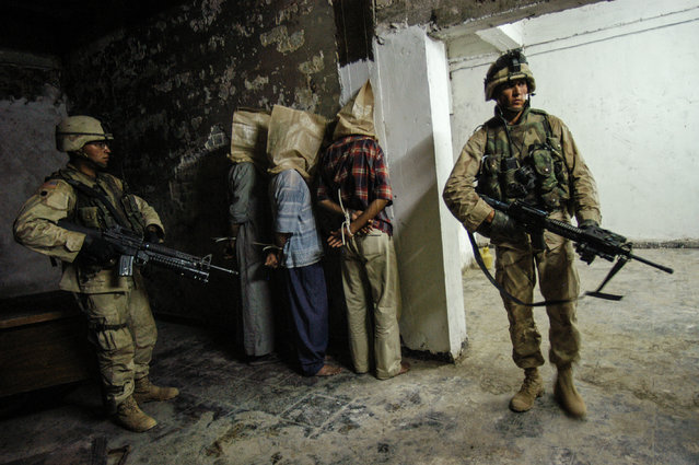 Iraqi men are detained, bound, and hooded in a compound during a night raid by troops with the 4th ID, 3rd Brigade, from the 1st Batallian-68th Armored Regiment American about 30 km North of Baghdad near Balad, Iraq,  June 29, 2003. (Photo by Lynsey Addario/Getty Reportage)