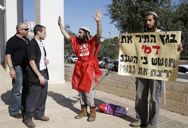 Court security guards watch as Israeli ultranationalists (R) protest against interrogation methods used by Israel's domestic security service, against suspects in a fatal arson attack in a West Bank village five months ago, during a court hearing in the case in Petah Tikva, Israel December 28, 2015. (Photo by Baz Ratner/Reuters)