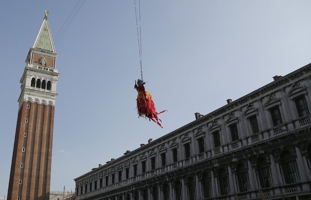 The traditional Columbine descends from Saint Mark's tower bell on an iron cable during the Venetian Carnival in Venice February 8, 2015. (Photo by Stefano Rellandini/Reuters)