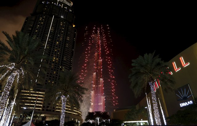 Fireworks explode over Dubai's Burj Khalifa, the tallest building in the world, during the New Year celebrations January 1, 2016, as the Address Downtown Dubai hotel and residential block, which had been engulfed by a fire, can be seen on the left. (Photo by Ahmed Jadallah/Reuters)