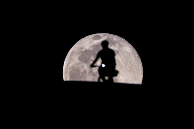 """A cyclist is silhouetted against the backdrop of a full moon, also known as """"Worm Moon"""", rises in Los Angeles, Sunday, March 28, 2021. (Photo by Ringo Chiu/ZUMA Wire/Rex Features/Shutterstock)"""