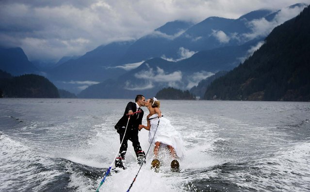 Newly weds Cam Auge and Caylee Wasilenko share a kiss as they waterski in Bedwell Bay in North Vancouver, British Columbia, after exchanging vows on the dock at the Vancouver Waterski Club, on August 28, 2013. (Photo by Jonathan Hayward/The Canadian Press)