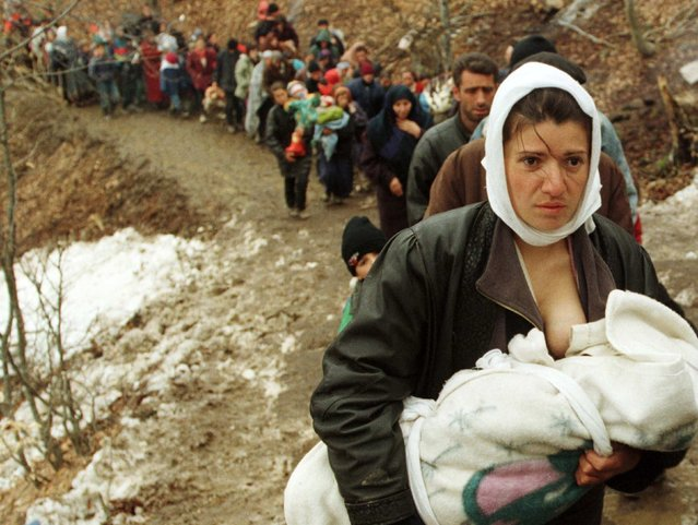 An ethnic Albanian woman feeds her baby as she and another 2,000 refugees, displaced by the war in Kosovo, are allowed to enter Macedonia in the mountainous region near the border crossing of Blace in this March 30, 1999 file photo. (Photo by Damir Sagolj/Reuters)