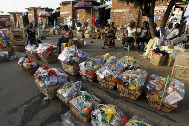 Women sit next to Christmas hampers for sale on the eve of Christmas at the Wuse market in Abuja, Nigeria December 24, 2015. (Photo by Afolabi Sotunde/Reuters)