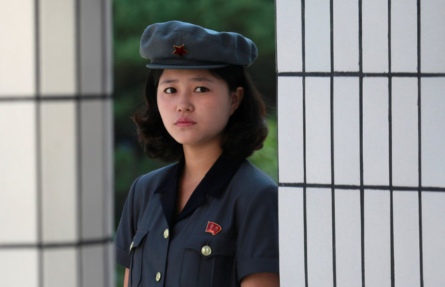 A woman guards stand at the gate of a cosmetic factory during a government organised visit for foreign reporters ahead of 70th anniversary of North Korea's foundation in Pyongyang, North Korea on September 8, 2018. (Photo by Danish Siddiqui/Reuters)