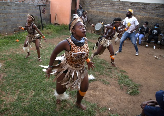 A group of girls perform traditional Zulu dance in the yard of a home in the Orange Farm Township south of Johannesburg, Wednesday, April 14, 2021. Amid the classes in dancing and marimba music, a leader of the culture group praised Britain's Prince Philip, who died last week and whose Duke of Edinburgh Awards helped to fund the culture group's activities. (Photo by Denis Farrell/AP Photo)