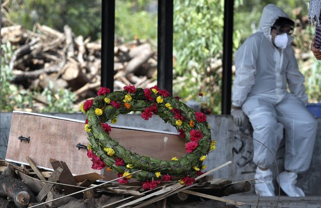 A wreath lies on the coffin of a COVID-19 victim before his cremation in Jammu, India, Friday, April 30, 2021.  Indian scientists appealed to Prime Minister Narendra Modi to publicly release virus data that would allow them to save lives as coronavirus cases climbed again Friday, prompting the army to open its hospitals in a desperate bid to control a massive humanitarian crisis. (Photo by Channi Anand/AP Photo)