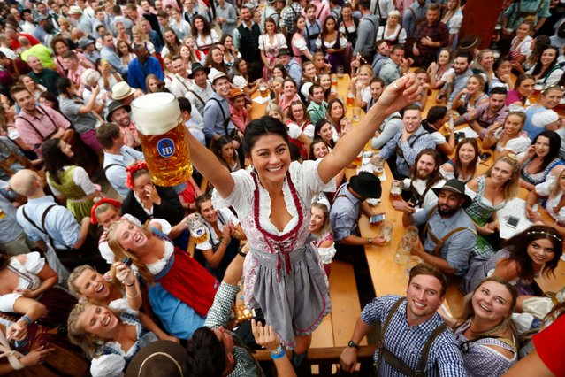 A young woman celebrates the opening of the 185th 'Oktoberfest' beer festival in Munich, Germany, Saturday, September 22, 2018. The world's largest beer festival will be held from Sept. 22 until Oct. 7, 2018. (Photo by Matthias Schrader/AP Photo)