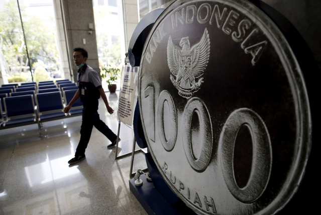 An employee walks past a mock one thousand rupiah coin on display at Bank Indonesia's headquarters in Jakarta, Indonesia April 21, 2016. (Photo by Darren Whiteside/Reuters)