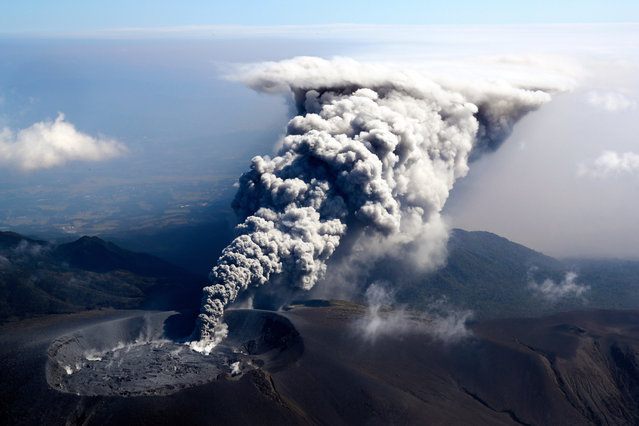 In this aerial image, volcanic ash spews from the crater of Mt. Shinmoedake on October 11, 2017 in Kirishima, Kagoshima, Japan. The eruption sends a plume of ash 300 meters into the air. The volcano, part of the Kirishima range in southern Kyushu, straddles the border of Miyazaki and Kagoshima prefectures. It previously erupted September 7, 2011. (Photo by The Asahi Shimbun via Getty Images)