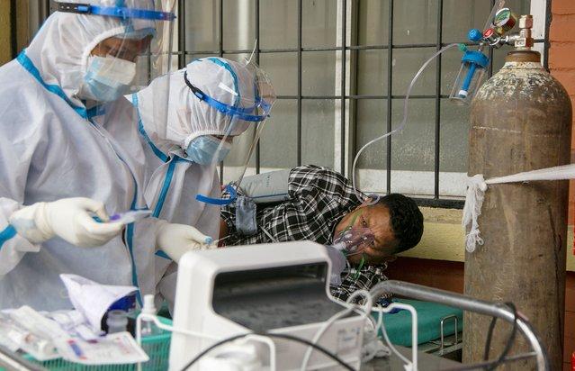 Nepalese paramedics treat a COVID-19 patient outside an emergency ward of a government run hospital in Kathmandu, Nepal, Friday, May 7, 2021. (Photo by Niranjan Shrestha/AP Photo)