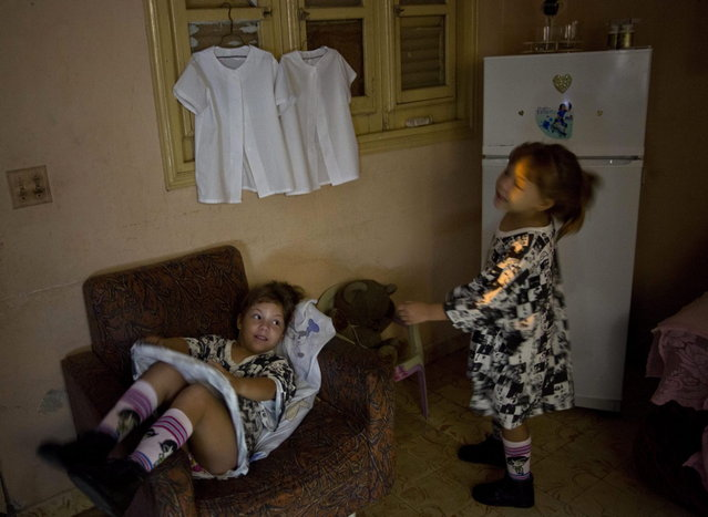 "In this September 23, 2013 photo, six-year-old twins Asley and Aslen Velazquez get ready for school in Havana, Cuba. Their mother Tamara said she never expected to have twins from her first pregnancy and did not take fertility treatments. ""It's a lot of work. It requires a lot of patience,"" Velazquez said. ""They are very active and dominant, although each has a different character"". (Photo by Ramon Espinosa/AP Photo)"