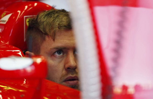 Ferrari Formula One driver Sebastian Vettel of Germany sits in his car in his garage during the first practice session of the Australian F1 Grand Prix at the Albert Park circuit in Melbourne March 13, 2015.  REUTERS/Brandon Malone