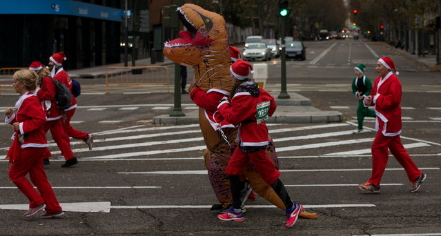 Participants, wearing Santa Claus outfits and a dinosaur costume, run during a charity race in benefit of the Multiple Sclerosis Foundation in Madrid, Spain, December 17, 2016. (Photo by Sergio Perez/Reuters)