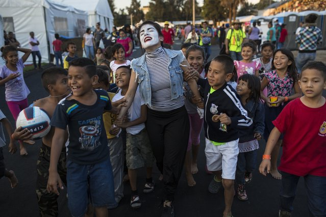 A woman performs as a mime for Central American migrant children at the Jesus Martinez stadium in Mexico City, Tuesday, November 6, 2018. Humanitarian aid converged around the stadium in Mexico City where thousands of Central American migrants winding their way toward the United States were resting Tuesday after an arduous trek that has taken them through three countries in three weeks. (Photo by Rodrigo Abd/AP Photo)