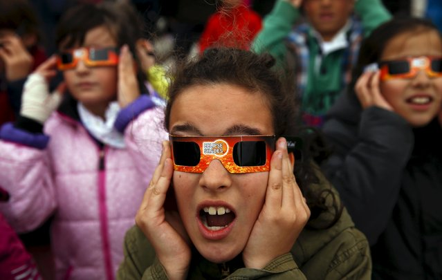 Schoolchildren react as they wear protective glasses to watch a partial solar eclipse, despite of the cloudy weather, at Madrid's Planetarium March 20, 2015. A solar eclipse swept across the Atlantic Ocean on Friday with the moon set to block out the sun for a few thousand sky gazers on remote islands with millions more in Europe, Africa and Asia getting a partial celestial show. (Photo by Sergio Perez/Reuters)