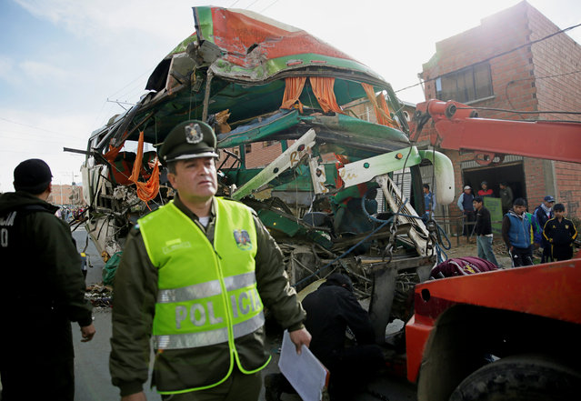 A police office stands next to wreckage of a bus that crashed into a semi-trailer, which resulted in multiple fatalities in Calajahuira on the outskirts of La Paz, Bolivia, December 23, 2016. (Photo by David Mercado/Reuters)