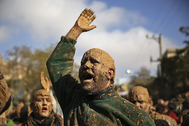 An Iranian Shiite is covered with mud during Ashoura rituals, marking the death anniversary of Imam Hussein, the grandson of Islam's Prophet Muhammad, at the city of Bijar, west of the capital Tehran, Iran, Thursday, November 14, 2013. (Photo by Ebrahim Noroozi/AP Photo)