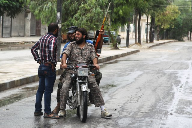 Free Syrian Army fighters on a motorbike chat with their friend in a rebel-controlled area of Aleppo, Syria, August 30, 2015. (Photo by Abdalrhman Ismail/Reuters)
