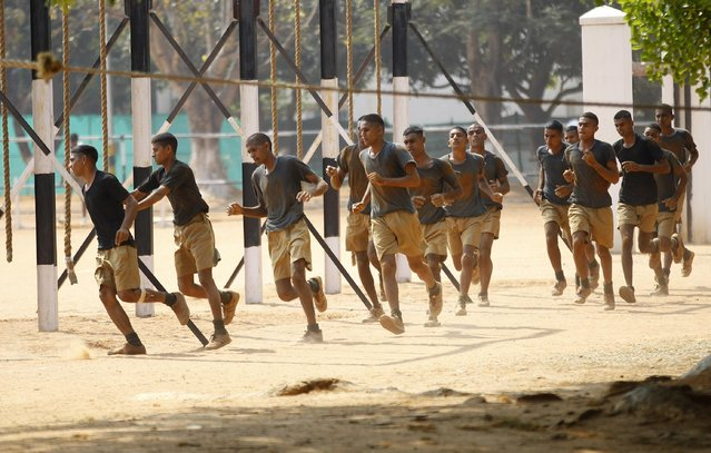 Newly recruited Indian army personnel run to participate in a training session in Bangalore, India, Wednesday, March 25, 2015. At a ceremony held earlier in the day, another batch of 292 recruits joined the ranks of the Indian army after successfully completing their training. (Photo by Aijaz Rahi/AP Photo)