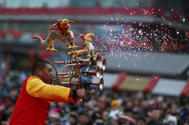 A performer plays an instrument at a temple fair in the beginning of Chinese Lunar New Year, at Huangsi Temple in Shenyang, Liaoning province, China February 8, 2016. (Photo by Sheng Li/Reuters)