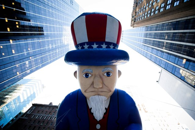 A giant Uncle Sam balloon is marched down 6th Avenue during the 87th Annual Macy's Thanksgiving Day Parade, Thursday, November 28, 2013, in New York. After fears the balloons could be grounded if sustained winds exceeded 23 mph, Snoopy, Spider-Man and the rest of the iconic balloons received the all-clear from the New York Police Department to fly between Manhattan skyscrapers on Thursday. (Photo by John Minchillo/AP Photo)