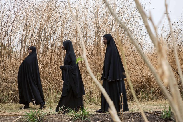 Women wearing black chadors attend the funeral of Omar Abdul Bakar, a young student who was killed on March 30 when soldiers shot into a crowd of young men on the side of the road in Kaduna, killing him and wounding four, in Kaduna on March 31, 2015. (Photo by Nichole Sobecki/AFP Photo)