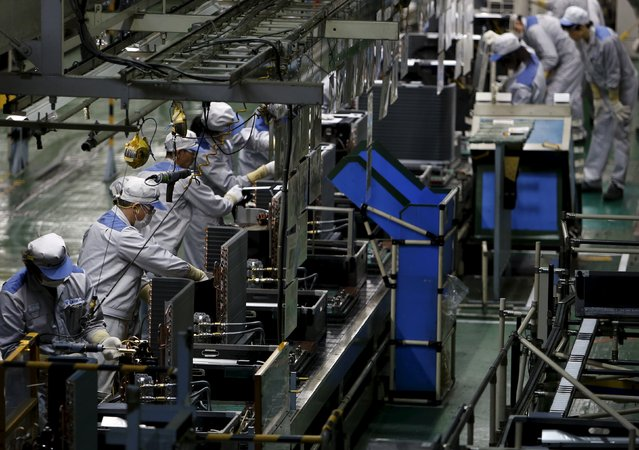 A Daikin Industries Ltd employee works the production line of outdoor air conditioning units at the company's Kusatsu factory in Shiga prefecture, western Japan March 20, 2015. (Photo by Yuya Shino/Reuters)