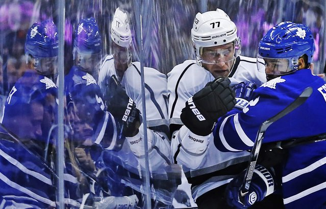 Toronto Maple Leafs' Mark Fraser, left, collides with Los Angeles Kings' Jeff Carter against a wall during first period NHL hockey action in Toronto on Wednesday, December 11, 2013. (Photo by Mark Blinch/AP Photo/The Canadian Press)