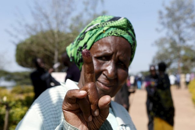 An elderly woman displays her inked finger after casting her vote during the presidential elections in Kirihura in western Uganda, February 18, 2016. (Photo by James Akena/Reuters)