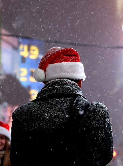 Snow falls on a man wearing a Santa Claus hat during a visit to Times Square on December 14, 2013. (Photo by Julio Cortez/Associated Press)