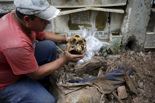A grave cleaner holds up a skull during exhumation works  at the General Cemetery in Guatemala City, April 15, 2015. (Photo by Jorge Dan Lopez/Reuters)