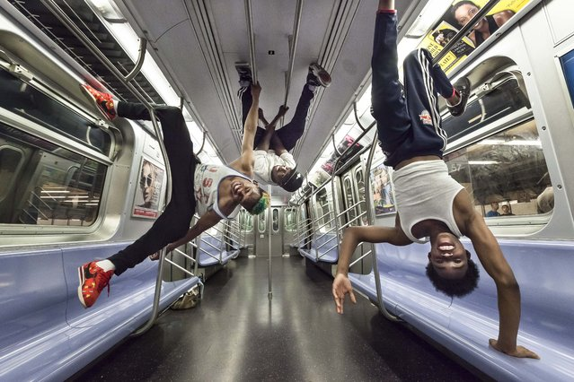 """(L-R) Andrew """"Goofy"""" Saunders, Dashawn Martin and Raymon """"Lex"""" Santos perform dynamic dance moves while hanging upside-down from the handrails in a New York City subway car. (Photo by Wiktor Skupinski/Barcroft Media)"""