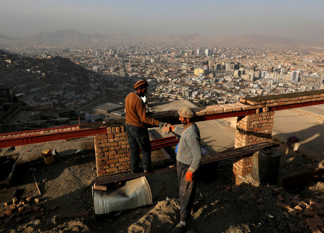 Afghan men build a house on a hilltop overlooking Kabul, Afghanistan January 1, 2017. (Photo by Mohammad Ismail/Reuters)